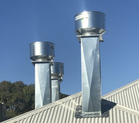 A set of commercial exhaust fans installed on top of a roof to ventilate a commercial kitchen canopy