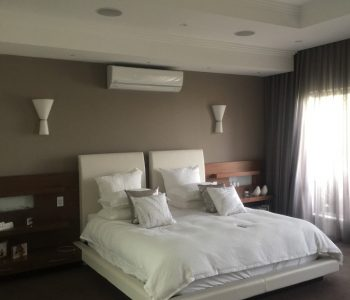 A bedroom with a split system air conditioning system installation over the bed